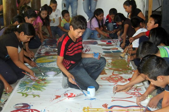 "Students at Miguel Angel Ramirez art school ""Casa Taller Encuentros"" painting a giant mural during workshop"